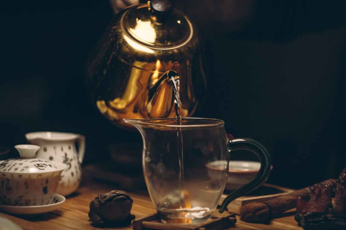 gold steel kettle beside clear glass pitcher