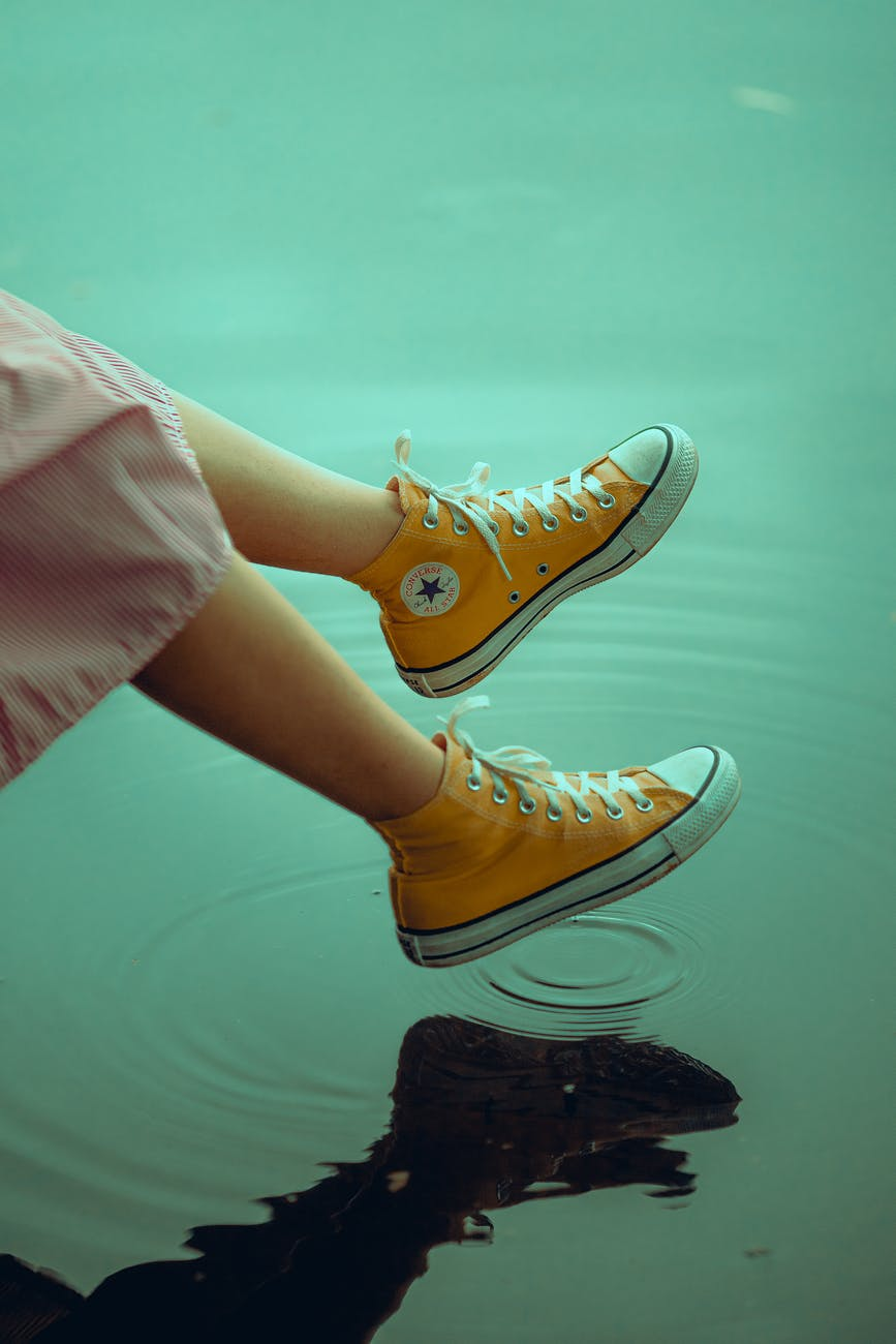 photo of person wearing yellow converse shoes